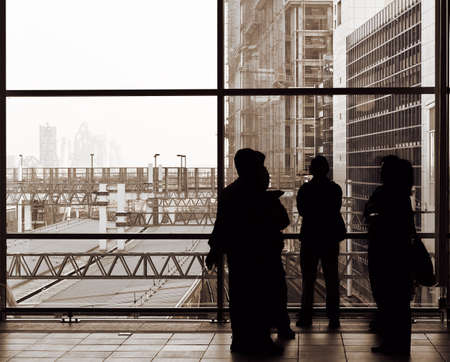 Businessman silhouette standing and talking in front of windows. photo