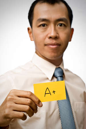 A plus sign on yellow card holding by businessman of Asian. photo