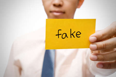 pinchbeck: Fake word on  yellow card holding by businessman.