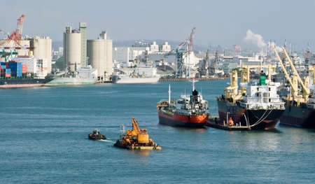 Cityscape of harbor with freighter on water of harbor and industry buildings in Kaohsiung, Taiwan. Stock Photo - 6636922