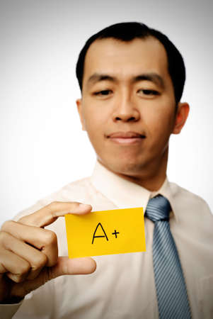 Successful businessman holding A+ card in yellow color. photo
