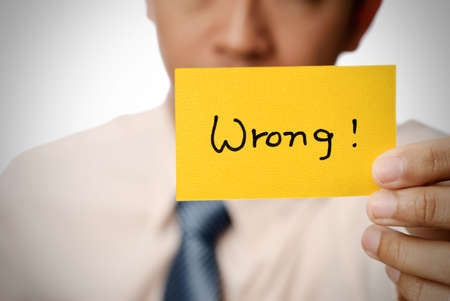 financial questions: Wrong words on yellow card holding by businessman.