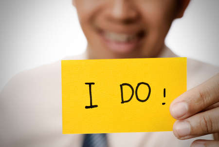 willing: Businessman holding yellow card showing words �V I do. Stock Photo
