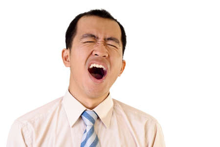 Tired businessman yawning with funny expression on white background. photo