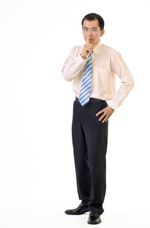 Asian businessman gesture with finger on lips showing silence sign and standing on white background. photo