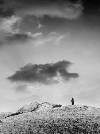 Dramatic landscape of lonely single man walking to mountain. photo