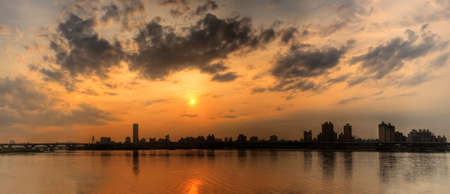 Panoramic cityscape of sunset scenery with building silhouette and river reflection under dramatic sky in dusk in Taipei, Taiwan.