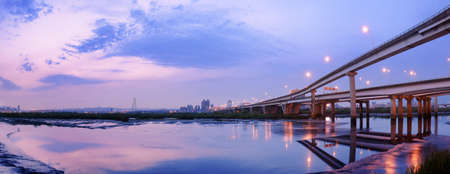 Panoramic cityscape with modern building and bridge under dramatic sky and illuminated reflection on sand and water of river in Taipei, Taiwan. photo
