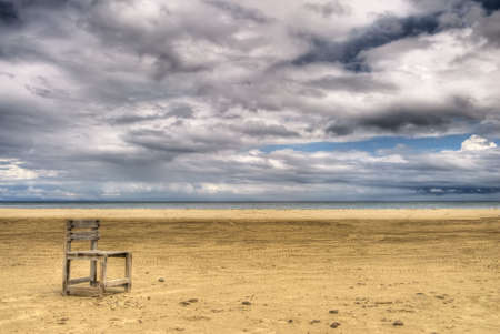 Alone scenic with single chair on yellow sand under white dramatic  clouds in sky. photo