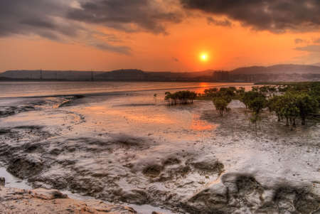 silt: Sunset scenic with red sun and silver silt of river in dusk. Stock Photo