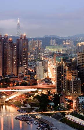 Panoramic cityscape of night with apartment near river bridge and famous landmark skyscraper in Taipei, Taiwan. photo