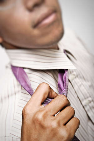 disengage: Businessman untie the tie for rest,closeup and focus on tie.