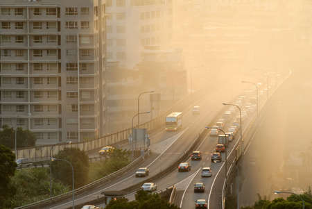 air view: Air pollution scenic with cars on highway and yellow smoke in city.