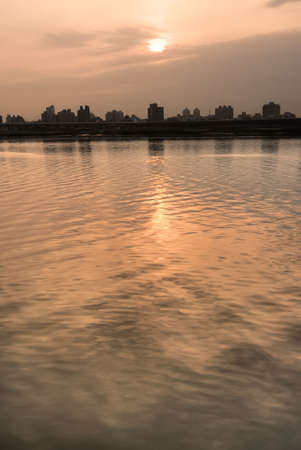 wavelet: City silhouette with sunset yellow color and water wavelet in river. Stock Photo