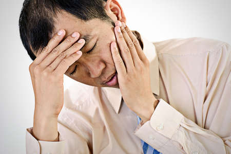 upset man: Sick businessman portrait of Asian with painful expression. Stock Photo