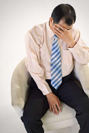 Sad business man sit on chair and cover face by hand. photo