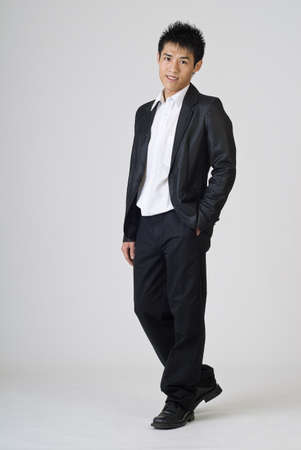 Full length portrait of Asian young businessman standing against gray. photo