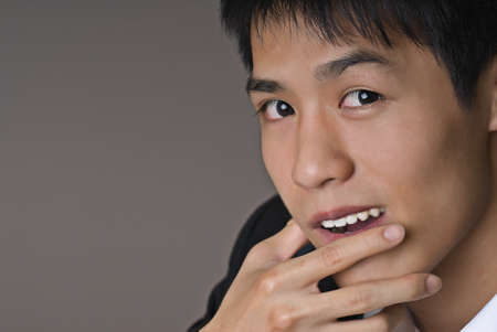 Smart young business man of Asian on gray background. photo