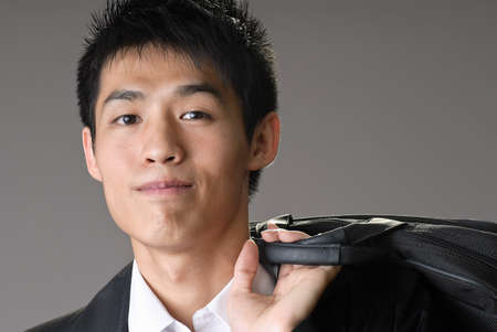 Portrait of young handsome business man of Asian with briefcase over shoulder. photo