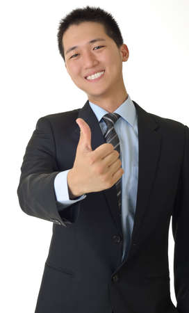 Smiling young business man of Asian giving you a thumbs up sign isolated against white. photo