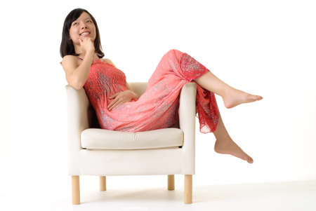 Asian lady sit on sofa at leisure with smiling expression on white background. Stock Photo - 7239618