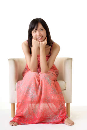 white women: Cute girl sit on sofa with pink dress isolated on white background. Stock Photo