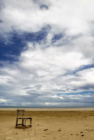 Lonely chair on beach with dramatic clouds. photo