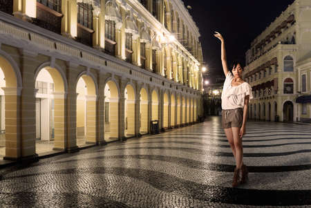 Lady dancing in street in night, Macao, China.