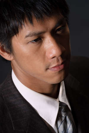 Closeup portrait of young business man, handsome Asian guy with lonely face. Stock Photo - 7325066