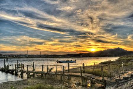 excitacion: Paisaje colorido del viejo muelle bajo cielo dram�tico en la puesta de sol.  Foto de archivo