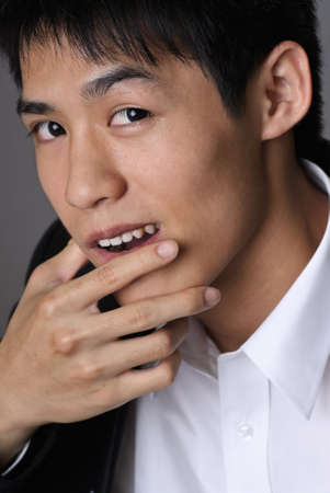 deceitful: Deceitful businessman face, closeup portrait of Asian man. Stock Photo