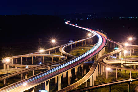 Freeway in night with cars light in modern city. photo