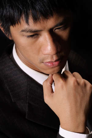 Thinking expression of oriental young business man, closeup portrait in dark background. photo