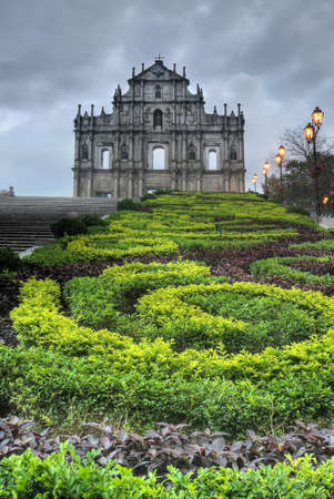 ruins is ancient: Macao landmark, ruins of St. Pauls Cathedral with green park in night in Macau, China. Stock Photo