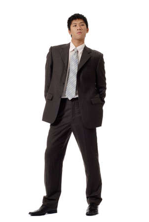 Business man of coldness, full length portrait of Asian office worker in formal suit standing and showing unfriendly expression, isolated on white background. Stock Photo - 7530066