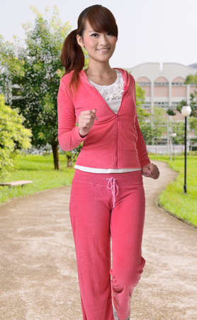 Cute girl jogging in the park of city with smiling face and happy expression. photo