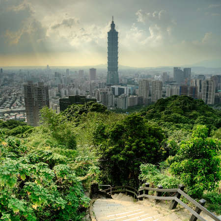 Dramatic cityscape of Taipei with famous landmark 101 skyscraper and trees in park, Taiwan, Asia.