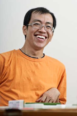 Happy smiling Asian man play Mahjong, traditional Chinese game. photo