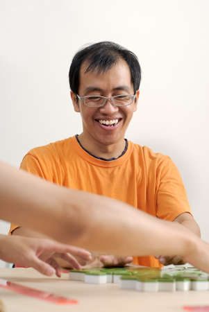Happy smiling Asian man play Mahjong with friends. photo