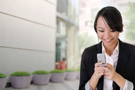 Happy business woman reading SMS and smiling outside of office building. Stock Photo - 7702397