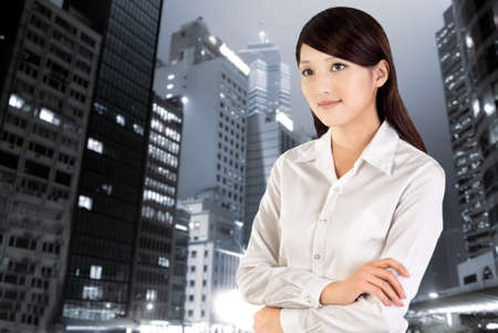asian office lady: Business woman in night, closeup portrait of Asian office lady standing outside with skyscrapers and edifices. Stock Photo