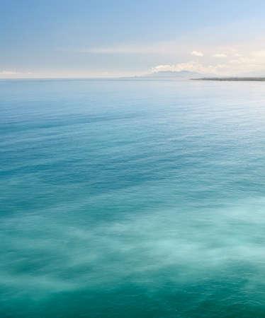푸른 하늘 아래 녹색 바다와 바다의 자연 배경. 스톡 콘텐츠