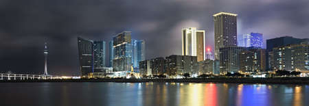 cities: Panoramic cityscape in night with skyscraper and buildings and river in Macao, China.