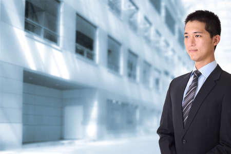 Asian young business man standing and looking in front of office buildings. photo