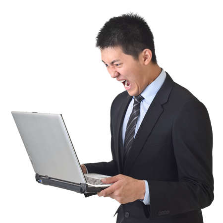 Angry business man holding laptop on white background. Stock Photo - 7904054