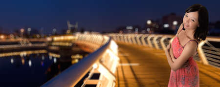 Attractive Asian woman with smiling expression standing on bridge in night in modern city. photo