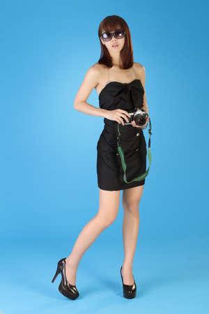při pohledu na fotoaparát: Fashion lady holding camera, full length portrait over blue background. Reklamní fotografie