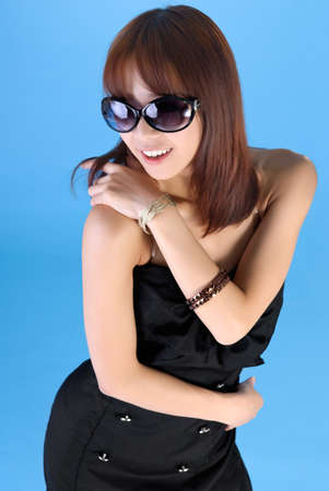 Modern woman of Asian with sunglasses over blue background. photo