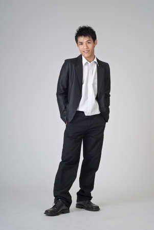 Young business man of Asian standing on studio gray background. photo