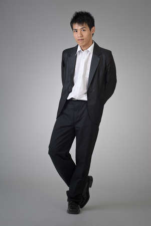 satisfied: Attractive Asian business man posing on studio gray background.